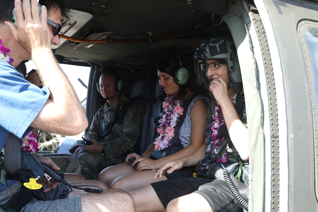 A teen and two family members sit in a helicopter wearing head gear and earphones.