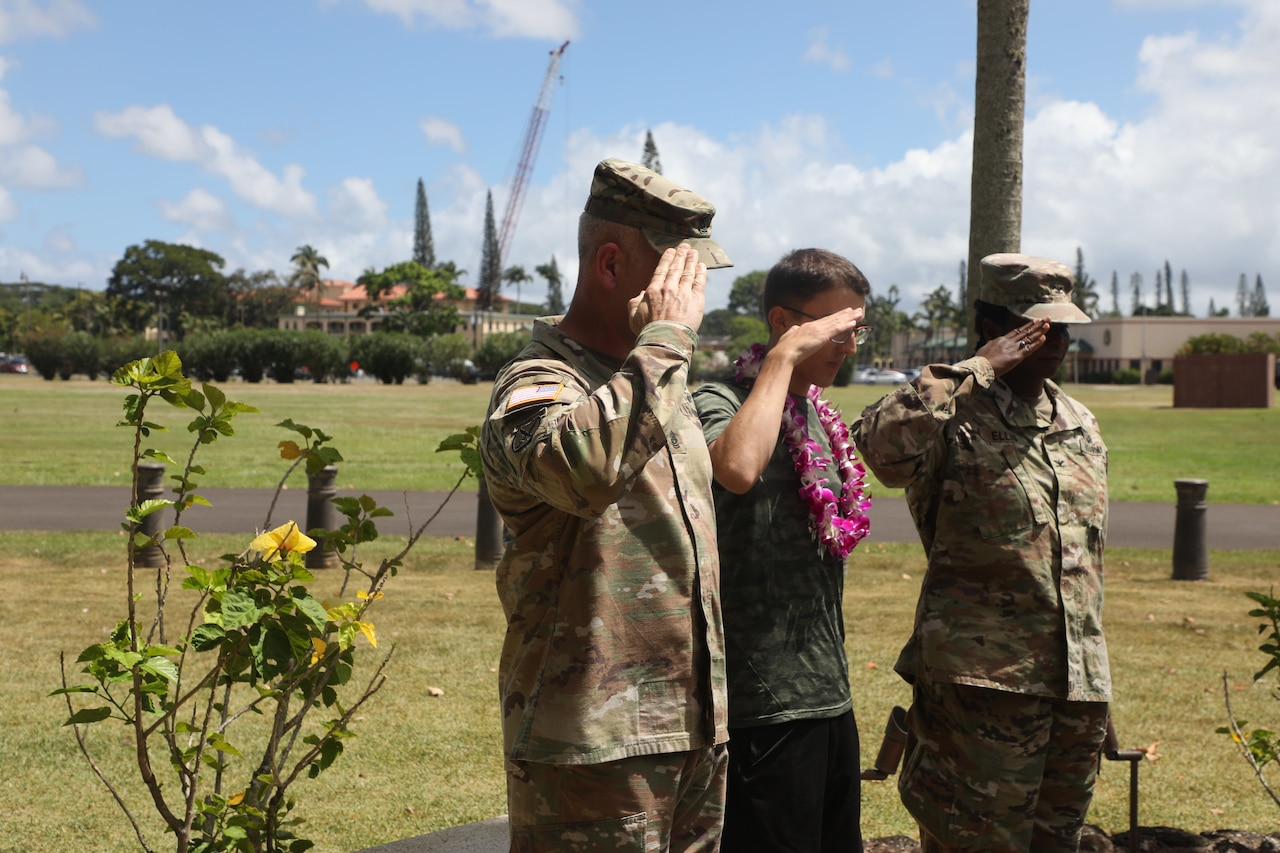 A teen wearing a Hawaiian lei and two soldiers salute an unseen object or person.