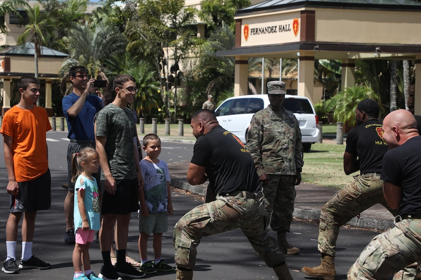 A family watches as several soldiers do a traditional Hawaiian warrior dance in front of them.