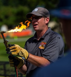 Deputy Chief Phil Higgins an instructor from P.L Vulcan Fire Training shows how to properly light and use a torch aboard Marine Corps Air Station Beaufort, July 25. P.L. Vulcan Fire Training is a team with combined over 40 years of experience in the fire and emergency services field who travel from Brooklyn, New York to teach different departments these lifesaving skills. (U.S. Marine Corps photo by Lance Cpl. Aidan Parker)