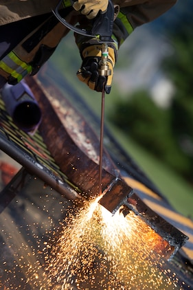 A firefighter from Marine Corps Air Station Beaufort Fire and Emergency Services cuts an iron plate using a burning rod of metal aboard Marine Corps Air Station Beaufort, July 25. This was taught to the first responders in order to combat full mechanical entrapment of a person. (U.S. Marine Corps photo by Lance Cpl. Aidan Parker)