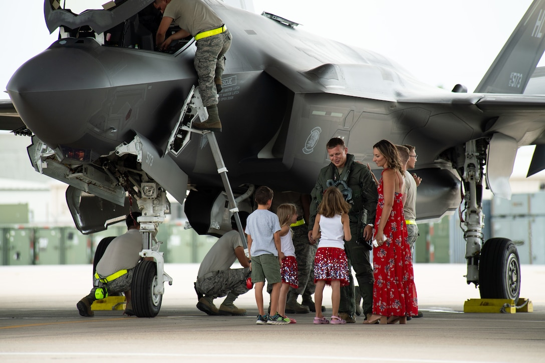 An F-35A Lightning II pilot with the 421st Fighter Squadron greets his family plane-side he returns from a deployment to Hill Air Force Base, Utah, July 31, 2019. The 421st Fighter Squadron participated in several combat exercises with allied and partner nations while deployed to Europe. (U.S. Air Force photo by R. Nial Bradshaw)