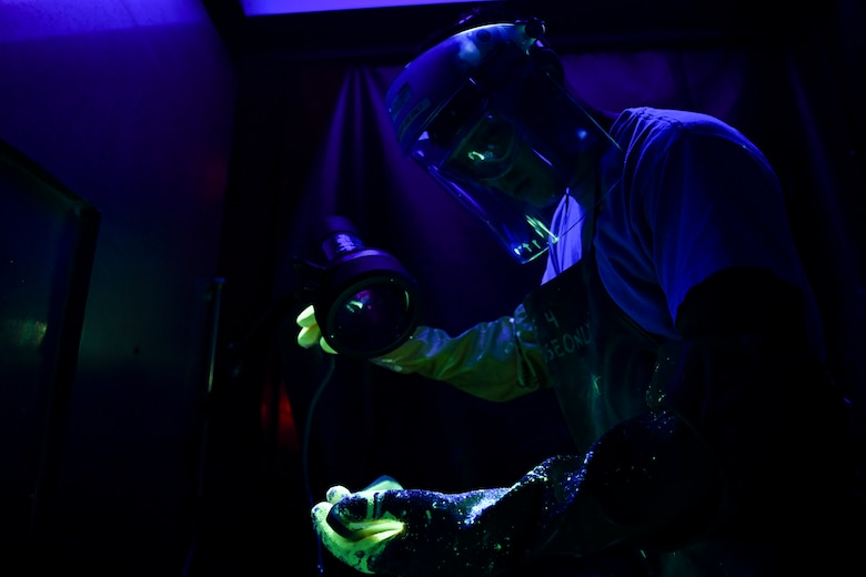 Specialist performs a fluorescent-penetrant inspection on an aircraft part