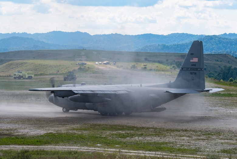 A C-130H Hercules lands on a dirt runway