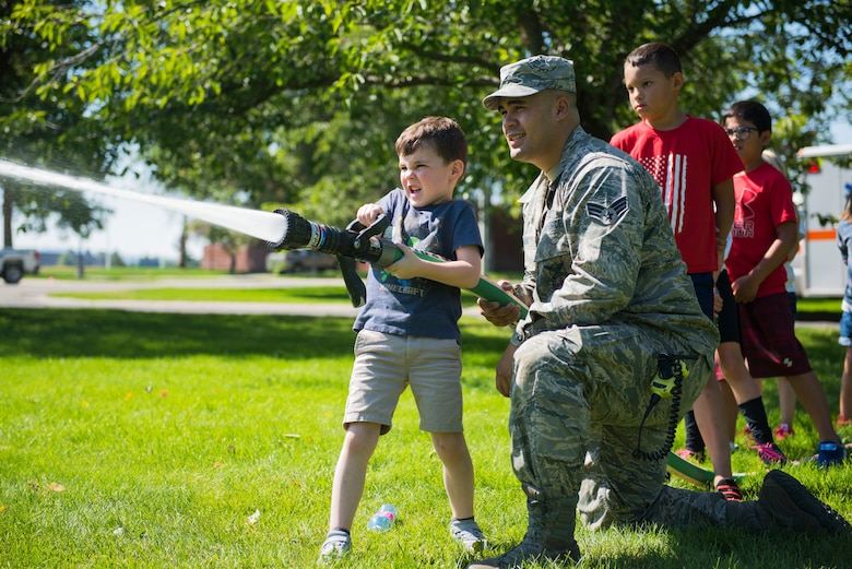 Senior Airman helps child operate a fire hose during Youth Fair