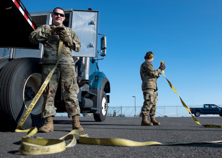 U.S. Air Force Senior Airmen Ben Hetzel and Ashley Pruitt, 92nd Logistics Readiness Squadron ground transportation journeymen, recoil cargo ratchet straps after unloading pallets of material during a Cargo Deployment Function exercise at Fairchild Air Force Base, Washington, July 24, 2019. Team Fairchild LRS Airmen practice quick cargo deployment often to execute air mobility support. (U.S. Air Force photo by Airman 1st Class Whitney Laine)