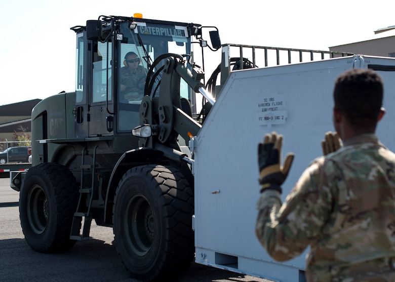 U.S. Air Force Senior Airman Dylan Oswalt, 92nd Logistics Readiness Squadron ground transportation journeymen, navigates cargo with a forklift during a Cargo Deployment Function exercise at Fairchild Air Force Base, Washington, July 24, 2019. Team Fairchild LRS Airmen practice quick cargo deployment often to execute air mobility support. (U.S. Air Force photo by Airman 1st Class Whitney Laine)