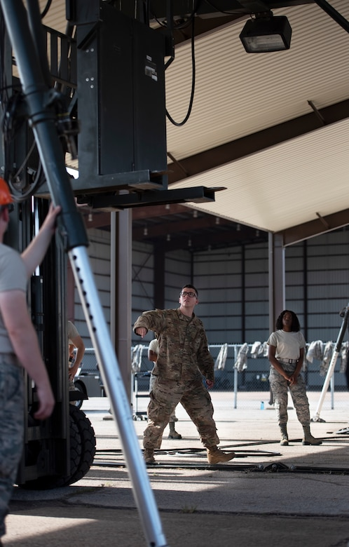 A 363rd Training Squadron munitions apprentice course instructor, center, guides another instructor as they work to build a munitions assembly conveyor at Sheppard Air Force Base, Texas, August 1, 2019. A MAC is used for convenience when a worksite may not have the right environment to set up a munitions shop. The MAC is used to create an assembly line anywhere if need be. (U.S. Air Force photo by Air Force photo by Airman 1st Class Pedro Tenorio)