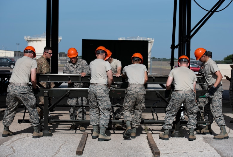 363rd Training Squadron munitions apprentice course students move a munitions assembly conveyor at Sheppard Air Force Base, Texas, August 1, 2019. The MAC can be assembled anywhere and is used in deployments to create an assembly line to build bombs anywhere if need be. This is only one part of the MAC and will be attached to other pieces for a longer conveyor. (U.S. Air Force photo by Air Force photo by Airman 1st Class Pedro Tenorio)
