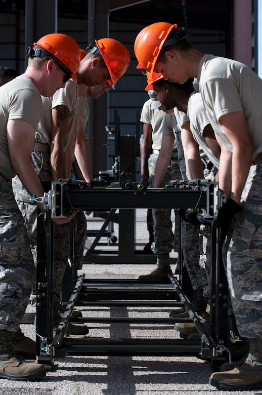 363rd Training Squadron munitions apprentice course students carry a munitions assembly conveyor at Sheppard Air Force Base, Texas, August 1, 2019. The students learn how to assemble a MAC and connect multiple MACs together to create a longer conveyor. They use these MACs to create assembly lines for bomb production and can be assembled in almost any area. (U.S. Air Force photo by Air Force photo by Airman 1st Class Pedro Tenorio)