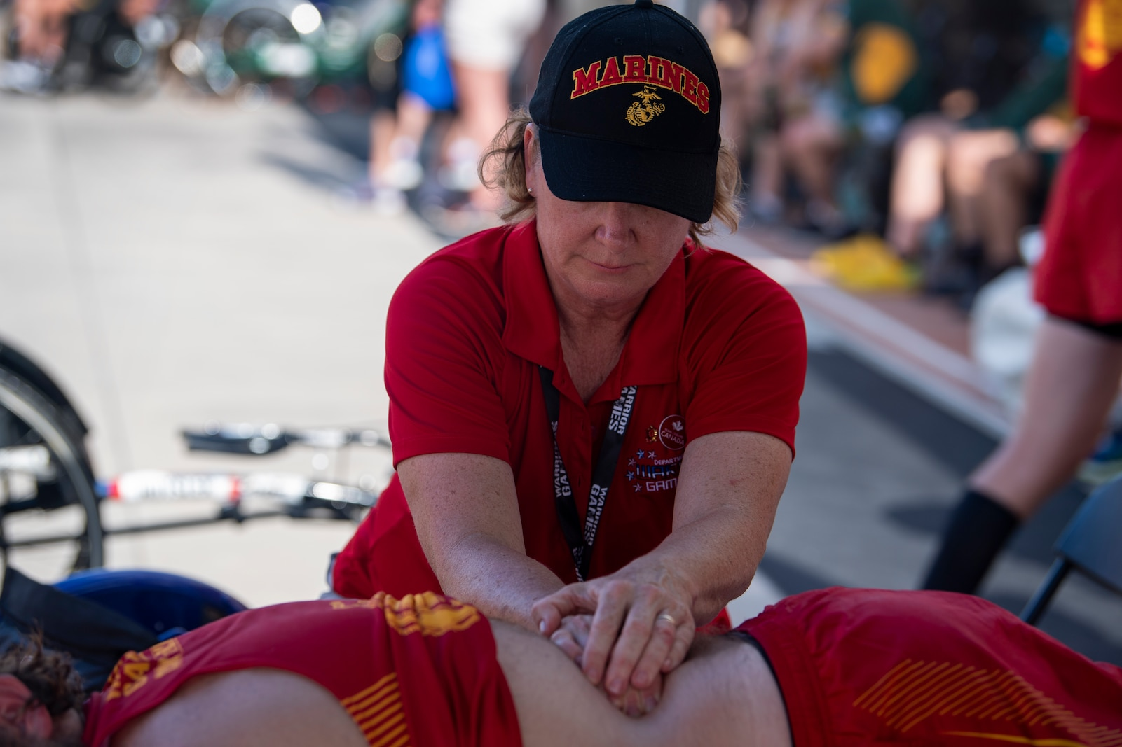 A team Marine Corps  medical staff member provides therapy to an athlete during the 2019 DoD Warrior Games. The Warrior Games showcase the resilient spirit of today's wounded, ill or injured service members from all branches of the military and provide a venue for recovering service members and veterans to demonstrate triumph over significant physical or invisible wounds and injuries.