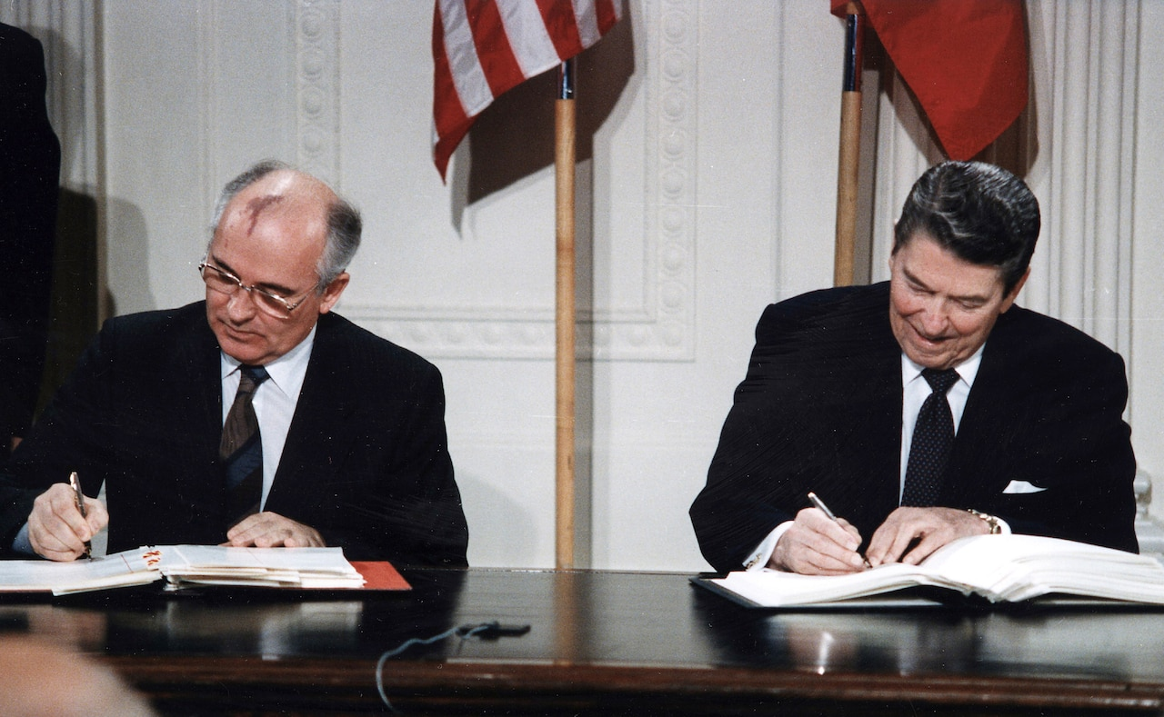 Two men sign documents at a desk.