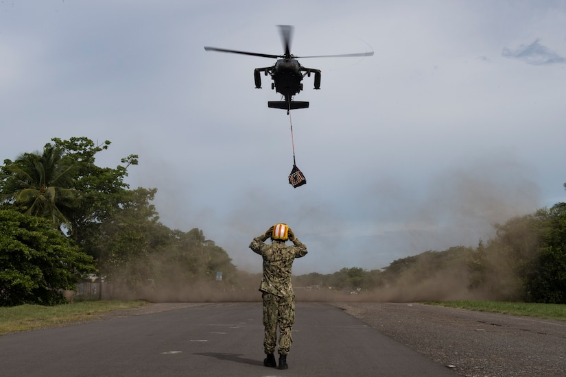 A U.S. Navy sailor deployed to the U.S.N.S. Comfort guides in a UH-60 Blackhawk carrying medical equipment and supplies July 21, 2019, Punta Arenas, Costa Rica. Pilots and aircrew assigned to the 1st Battalion, 228th Aviation transported personnel and equipment to allow the U.S. Naval Ship Comfort to provide medical care to Costa Rican citizens and Venezuelan migrants as part of the United States enduring promise of helping its southern neighbors. The Winged Warriors transported more than 470 people and 20 tons of cargo from July 21 - 30. (U.S. Air Force photo by Staff Sgt. Eric Summers Jr.)
