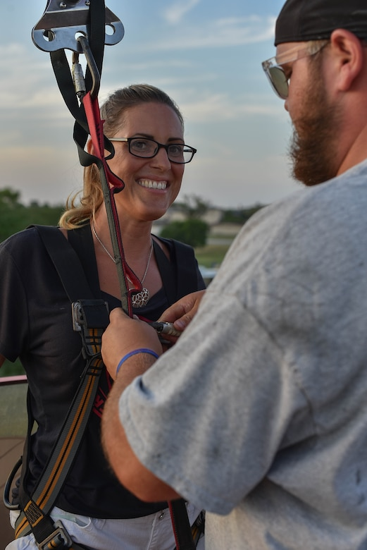 Master Sgt. Amy Watkins, Family Health flight chief, is fitted for a zipline