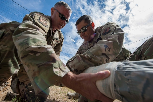 Maj. Christopher Lopes and Tech. Sgt. John Castillo, both members, assigned to the 149th Medical Group, apply a splint to an actor during Tactical Combat Casualty Care training at Coast Guard Station Lake Tahoe, Nevada June 16.