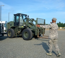 Tech. Sgt. Terry Cooper, 507th Logistics Readiness Squadron ground transportation quality assurance, guides the driver of an all-terrain forklift July 18, 2019, at Joint Base Elmendorf-Richardson, Alaska. (U.S. Air Force photo by Tech. Sgt. Samantha Mathison)