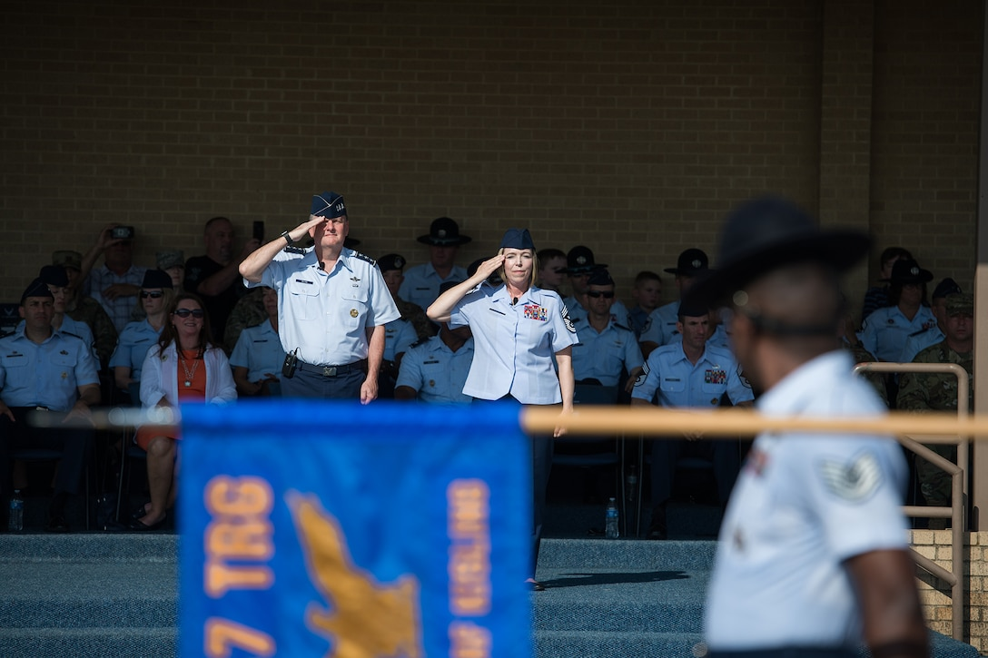 U.S. Air Force Lt. Gen. Brad Webb (right), commander of Air Education and Training Command (AETC), and Chief Master Sgt. Julie Gudgel, AETC command chief, salute basic military trainees during the graduation parade Aug. 2, 2019, at Joint Base San Antonio-Lackland, Texas