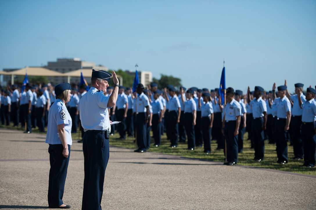 U.S. Air Force Lt. Gen. Brad Webb (right), commander of Air Education and Training Command (AETC), gives the oath of enlistment to graduating Airmen Aug. 2, 2019, at Joint Base San Antonio-Lackland, Texas.