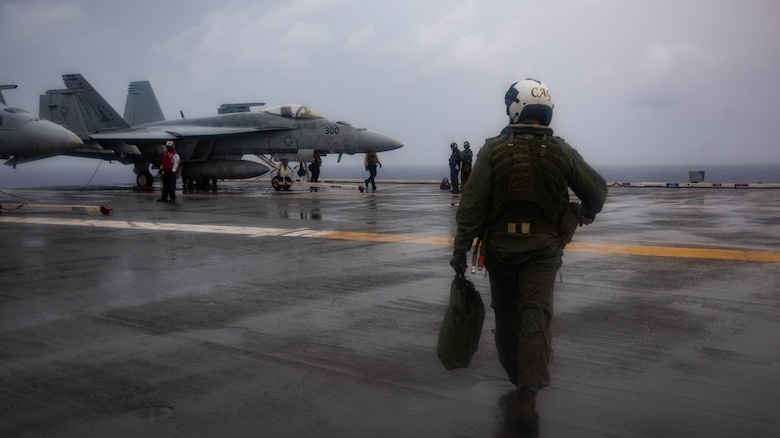 PHILIPPINE SEA (August 2, 2019) Capt. Forrest Young, Commander, Carrier Air Wing 5, walks toward his aircraft on the flight deck of the Navy's forward-deployed aircraft carrier USS Ronald Reagan (CVN 76) prior to conducting an in-flight change of command ceremony. Young was relieved as commanding officer of Carrier Air Wing (CVW) 5 by Capt. Michael Rovenolt. Ronald Reagan, the flagship of Carrier Strike Group Five, provides a combat-ready force that protects and defends the collective maritime interests of its allies and partners in the Indo-Pacific region.