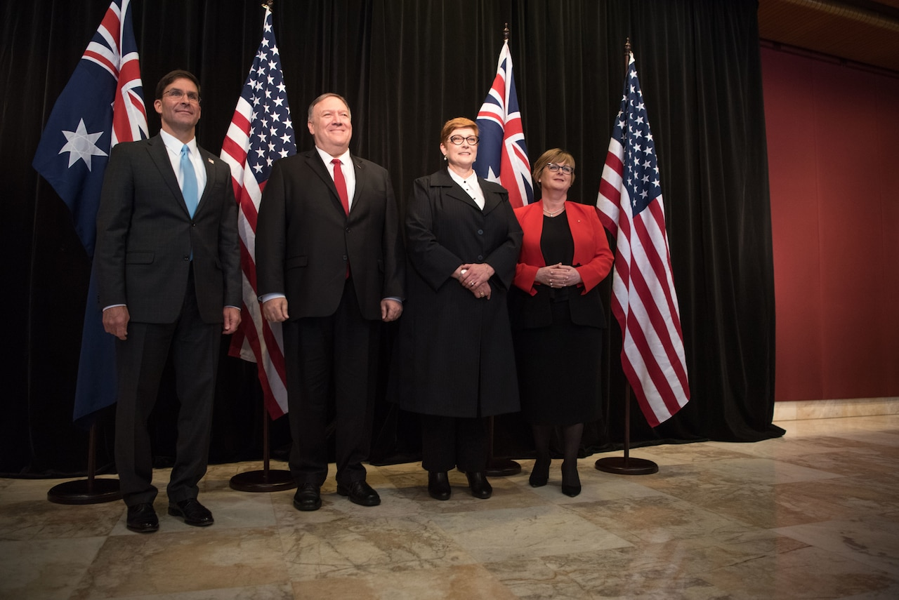 Four people in a line before U.S. and Australian flags