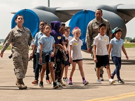 Two Airmen with  a group of children walking on the flight line with a plane visible in the background