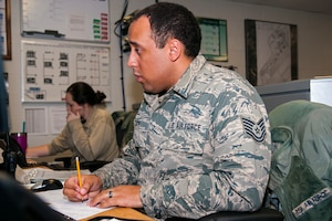 Airman taking notes on a desk with classroom in the background