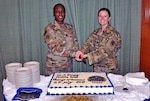 two women in uniform prepare to cut a cake