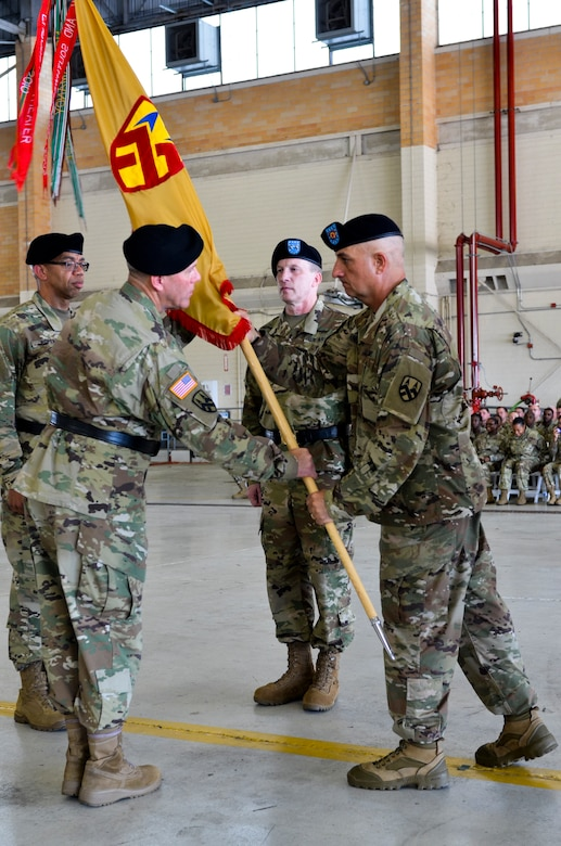 The 377th Theater Sustainment Command's senior enlisted leader, Command Sgt. Major Lawrence Arnold, passes the unit colors to outgoing commander, Maj. Gen. Steven Ainsworth during a change of command ceremony at Naval Air Station Joint Reserve Base New Orleans August 3, 2019.