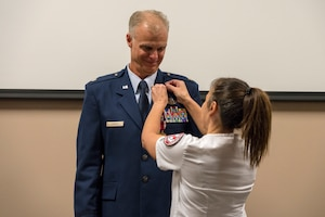 Shelly Gibson pins the U.S. Air Force retirement pin on her husband Lt. Col. Keith Gibson, 403rd Wing Operations Group deputy commander, during his retirement ceremony Aug. 3, 2019 at Keesler Air Force Base, Mississippi. Gibson completed his Air Force career with 29 years of service. (U.S. Air Force photo by Tech. Sgt. Christopher Carranza)