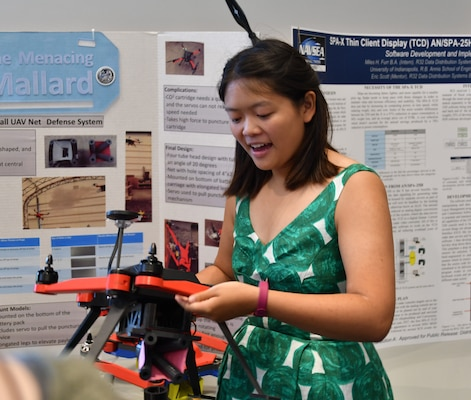 IMAGE: DAHLGREN, Va. (July 25, 2019) — University of Virginia junior Kimberly Louie explains how the deck-gun she helped create and attach to a drone operates while briefing to military and government personnel during her 2019 summer internship. Louie was among 20 students who completed their internships at Naval Surface Warfare Center Dahlgren Division (NSWCDD). The Naval Research Enterprise Internship  Program (NREIP) encourages students to pursue science and engineering careers, furthers education via mentoring and their participation in research, and makes them aware of Navy research and technology efforts, which can lead to civilian employment within the Navy.