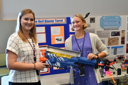IMAGE: DAHLGREN, Va. (July 25, 2019) — Margot Adams (left) and Chaney Ganninger brief attendees on their integration of a Nerf gun into an autonomous turret gun system. They were among students who completed their summer internships at Naval Surface Warfare Center Dahlgren Division. The Science and Engineering Apprenticeship Program (SEAP) encourages participating high school students to pursue science and engineering careers, to further their education via mentoring by laboratory personnel and their participation in research, and to make them aware of DoN research and technology efforts, which can lead to employment within the DoN.