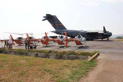 Five helicopters sit on the tarmac at Bogota El Dorado International Airport.