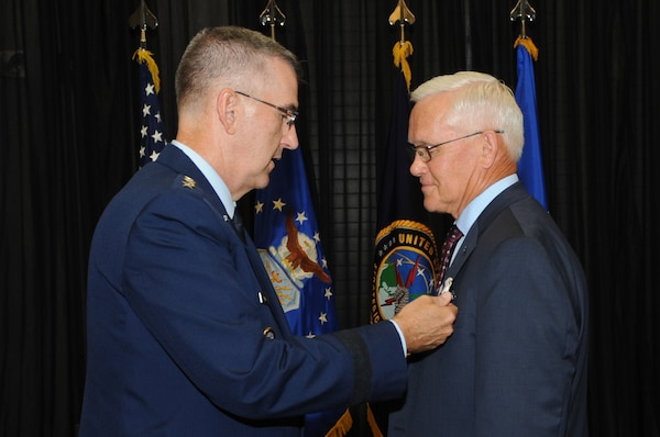 U.S. Air Force Gen. John Hyten, commander of U.S. Strategic Command, presents the Joint Distinguished Civilian Service Award  to Pat McVay, director of joint exercises, training and assessments, and a Senior Executive Service member, during his retirement ceremony in Bellevue, Neb., July 26, 2019.