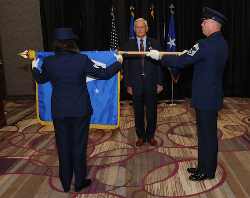 U.S. Air Force members Staff Sgt. Grace Gonzalez (left) and Chief Master Sgt. Richard Dawson (right) furl Pat McVay's (center), director of joint exercises, training and assessments, Senior Executive Service flag during his retirement ceremony in Bellevue, Neb., July 26, 2019.