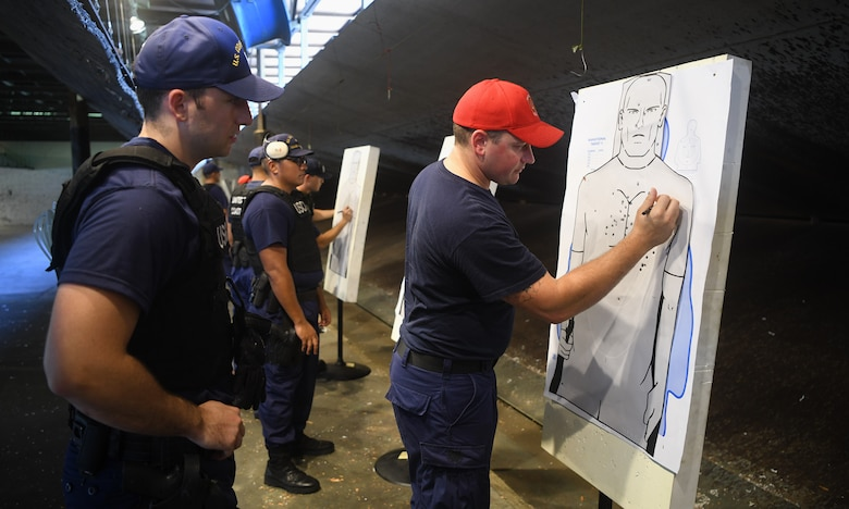 U.S. Coast Guard Petty Officer 1st Class Christopher Thomas, USCG Sector Charleston armory lead petty officer, right, evaluates the performance of Ensign Oliver Kremer, USCG Cutter Hamilton law enforcement officer, left, at Joint Base Charleston, S.C., Aug. 1, 2019. Coast Guard combat arms instructors from USCG Sector Charleston assisted in the evaluation of the guardsmen to ensure they were ready and worldwide qualified for their next mission. Combat Arms Training and Maintenance instructors support the readiness of Joint Base Charleston's mission partners through training and evaluating service members on proficiently operating and safely handling their weapons. The partnership between Air Force and Coast Guard personnel supports USCG Sector Charleston in their mission of performing maritime safety, security and stewardship in their area of responsibility.