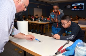 Gregory Fletcher, Southwest Research Institute Space, Science, and Engineering Division senior program manager, guides Starbase Kelly summer camp students through an experiment at the Southwest Research Institute in San Antonio, Texas, July 31, 2019.