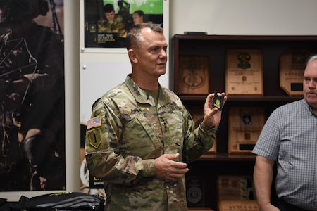 Gen. Paul Funk II, commanding general of U.S. Army Training and Doctrine Command, discusses the personal presentation items produced by the U.S. Army Marketing Engagement Brigade during a visit to the brigade headquarters at Fort Knox, Kentucky, Aug. 1. The MEB's mission is to support Army accessions. The unit does a variety of support operations, one being the production of presentation items for both U.S. Army Recruiting Command and U.S. Army Cadet Command. This was Funk's first visit to the brigade since taking command of TRADOC. (U.S. Army photo by Lara Poirrier)
