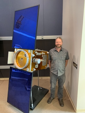 Daniel Engelhart of Assurance Technology Corporation, displays a scale model of satellite XSS-11 which uses Kapton to manage the internal temperature of the satellite. Electron irradiation alters the optical and mechanical properties of the material, leading to non-ideal spacecraft thermal management. (Courtesy photo)