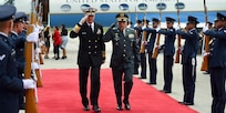 Military leaders salute while walking.
