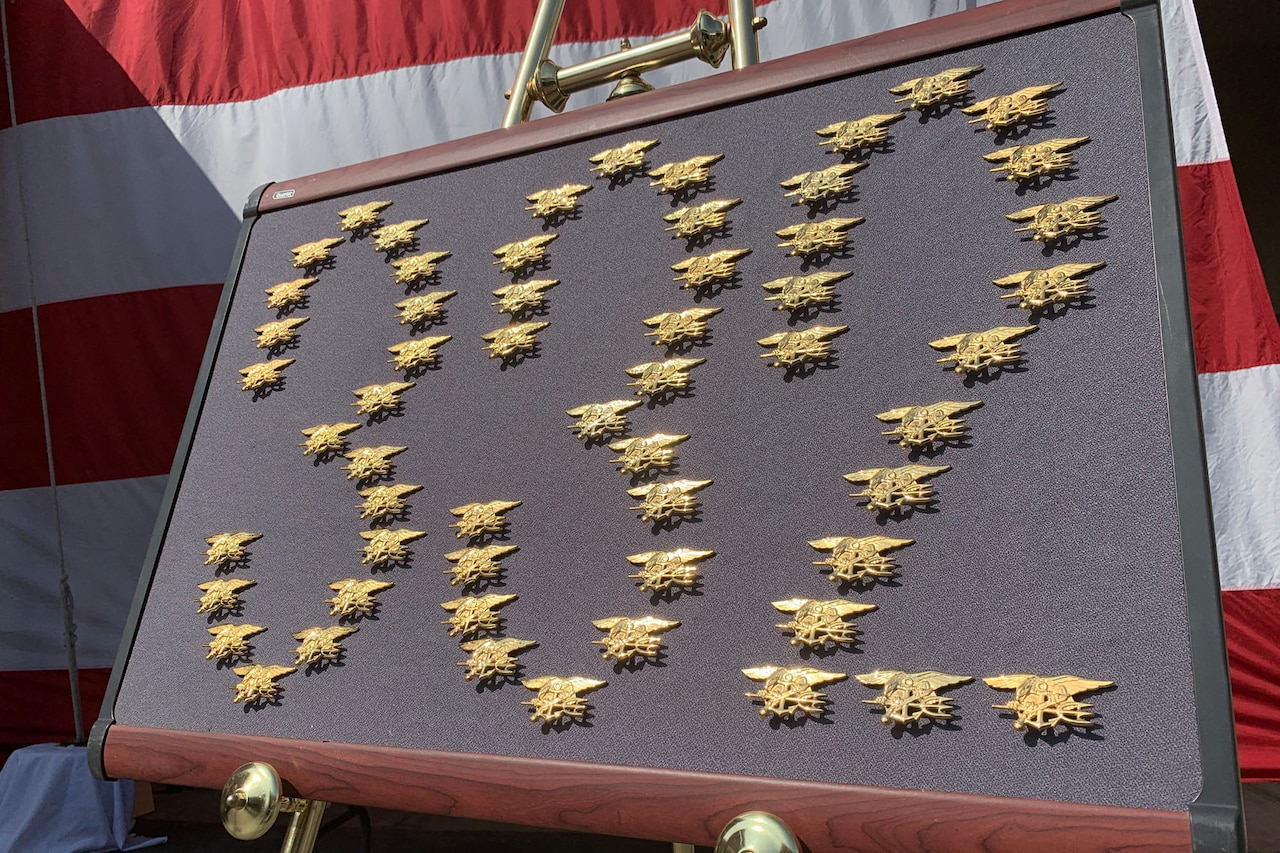 Gold pins form the number 332 on a framed display.