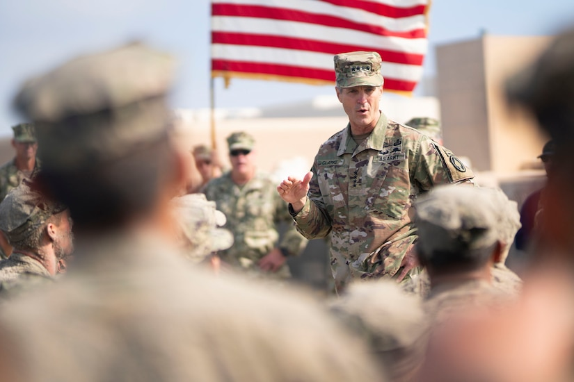 An Army officer in camouflage uniform speaks to seated men with an American flag in the background.