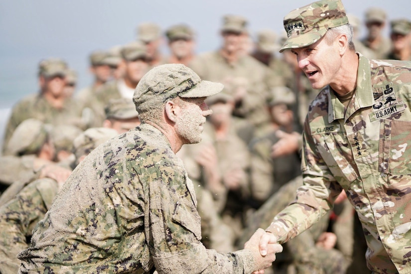 An Army officer shakes hands with a sand-covered sailor. Both are in camouflage uniforms.