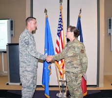 Col. Lisa M. Craig, Air Force Reserve Command director of manpower, personnel, and services, presents a coin to Master Sgt. Brian Boblett, 433rd Force Support Squadron family readiness NCO, Aug 3, 2019 at Joint Base San Antonio-Lackland, Texas.