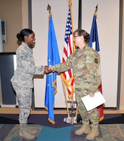 Col. Lisa M. Craig, Air Force Reserve Command director of manpower, personnel, and services, presents a coin to Staff Sgt. Chelsea Smith, 433rd Force Support Squadron sustainment specialst, Aug 3, 2019 at Joint Base San Antonio-Lackland, Texas.