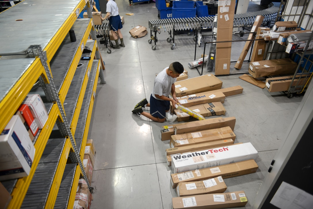 Airman 1st Class Valeriano DeLeon III, a military postal clerk from the 31st Force Support Squadron, labels packages to be placed on the shelf from an early morning shipment, Aug. 2, 2019, at Aviano Air Base, Italy. DeLeon worked the first morning shift where they unloaded a semi-truck of mail. (U.S. Air Force photo by Airman 1st Class Ericka A. Woolever)