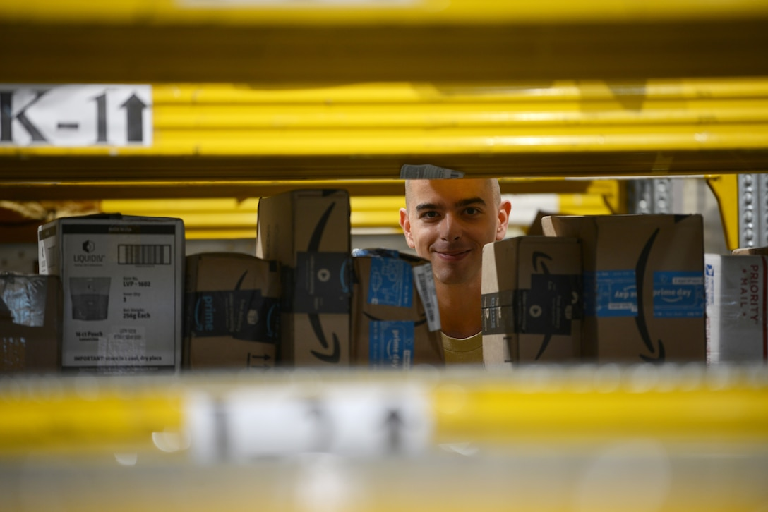 Airman 1st Class Dylan Cooper, a military postal clerk from the 31st Force Support Squadron, poses for a picture as he places a package on a shelf, Aug. 2, 2019, at Aviano Air Base, Italy. Cooper scanned and labeled various packages from an early morning shipment. (U.S. Air Force photo by Airman 1st Class Ericka A. Woolever)