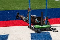 Capt. Chandler Smith, a member of the U.S. Warrior Fitness Team, competes in the men's individual competition at the 2019 CrossFit Games in Madison, Wis., Aug. 2 2019. During the fourth round, Smith had to complete a 172-foot sled push, 18 bar muscle-ups, and another 172-foot sled push to the finish line in under six minutes. (Photo Credit: Devon L. Suits)