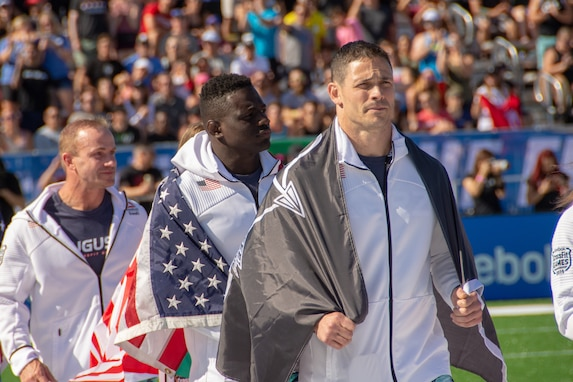 Lt. Col. Anthony Kurz and Capt. Chandler Smith, representing the U.S. Army Warrior Fitness Team, march onto the field during the 2019 CrossFit Games opening ceremony in Madison, Wis., Aug. 1, 2019. Kurz proudly displayed his U.S. Army Special Forces flag as a nod to the Special Forces community. (Photo Credit: Sgt. 1st Class Robert Dodge)