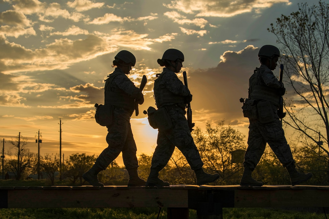 Three Air Force trainees, shown in silhouette, walk in a line.