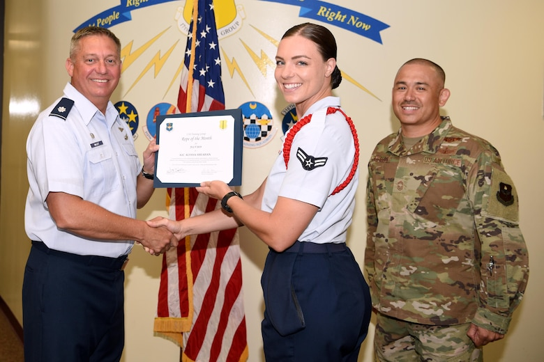 U.S. Air Force Lt. Col. Herbert Millet III, 313th Training Squadron commander, presents the 312th Training Squadron Student of the Month award to Airman 1st Class Alyssa Sheahan, 312th TRS student, at the Brandenburg Hall on Goodfellow Air Force Base, Texas, August 2, 2019. The 312th TRS's mission is to provide Department of Defense and international customers with mission ready fire protection and special instruments graduates and provides mission support for the Air Force Technical Applications Center. (U.S. Air Force photo by Airman 1st Class Abbey Rieves/Released)